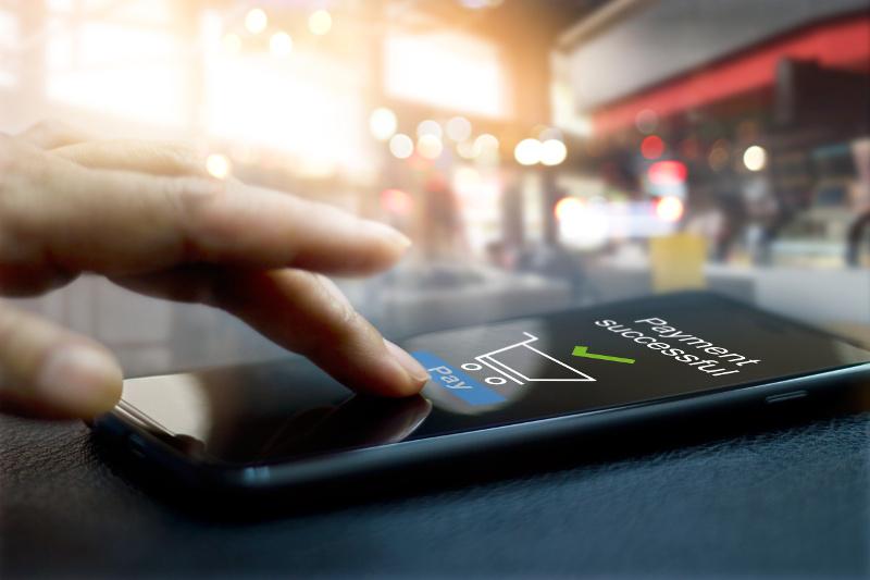 スマートフォンで支払いが完了した画面とスマホを操作する指
