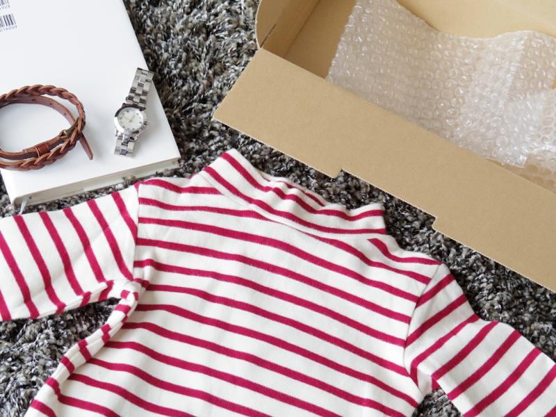 床に置かれたシャツと宅配用のダンボール箱